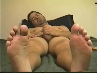In bed jerking off with my sweaty feet in your face!